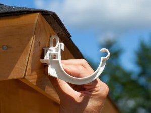 Een witte dakgoot beugel op een gootwighoekje